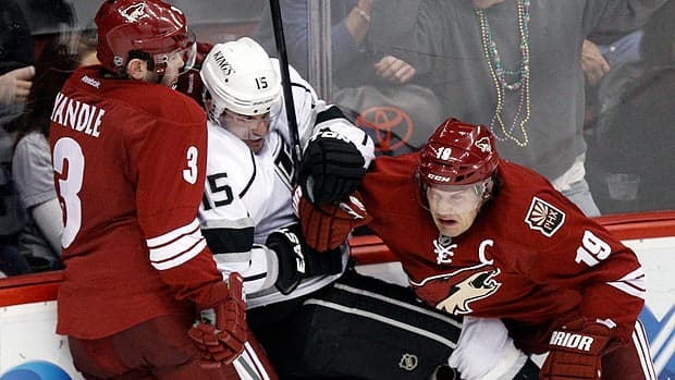 Los Angeles Kings centre Brad Richardson, center, is sandwiched between Phoenix Coyotes defence eman Keith Yandle, left, and right wing Shane Doan during a game in February. (Paul Connors/Associated Press)