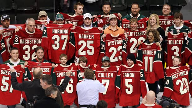 Minnesota Wild fans, shown in this 2011 file photo, hold game-worn sweaters from Minnesota Wild players. The team will have Zach Parise and Ryan Suter jerseys to hand out for the next few years after the two signed identical 13-year deals on Wednesday. (File/Reuters)