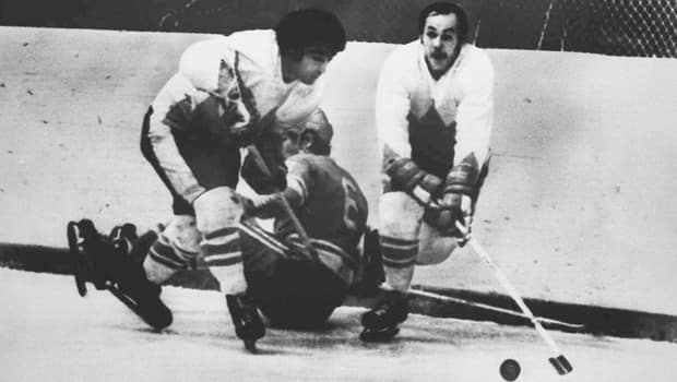 Team Canada forwards J.P. Parise, left, and Yvan Cournoyer strip Valeri Vasiliev of the puck in Game 6 on Sept. 24, 1972. (Canadian Press)