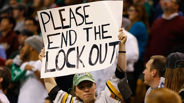 We wonder how this Bruins fan, holding up a 'Please end the lockout' sign at a Celtics game earlier this month, is reacting to the news that mediators will get involved in the NHL labour talks.  (Jared Wickerham/Getty Images)