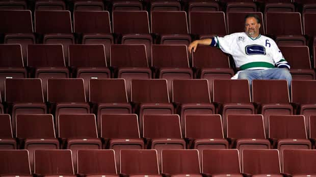 A Vancouver Canucks fan sits in empty seats after Game Seven of the 2011 NHL Stanley Cup Final at Rogers Arena on June 15, 2011. (Rich Lam/Getty Images)