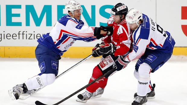 Team Canada's Jacob Micflikier, centre, vies for the puck with Adler Mannheim's Luca Sbisa, left, and Marc El-Sayed during the Spengler Cup in Davos, Switzerland on Wednesday. (Salvatore Di Nolfi, Keystone/Associated Press)