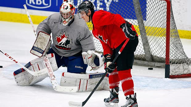 Goalie Laurent Brossoit, left, from Surrey, B.C., looks on as Mark Scheifele, stickhandles the puck during selection camp in Calgary on Tuesday. (Jeff McIntosh/Canadian Press)