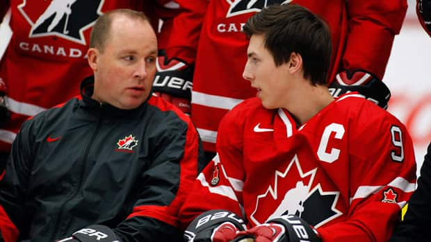 Canadian junior head coach Steve Spott, left, confers with captain Ryan Nugent-Hopkins during a team photo session. (Jeff McIntosh/Canadian Press)