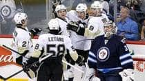 Pittsburgh Penguins sniper Sidney Crosby, centre, celebrates the first of his two goals on Winnipeg Jets goaltender Ondrej Pavelec on Friday. (John Woods/Canadian Press)