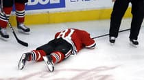 Chicago Blackhawks winger Marian Hossa (81) lays on the ice after being hit in the back of the head by Vancouver Canucks winger Jannik Hansen during the third period Tuesday. (Charles Rex Arbogast/Associated Press)
