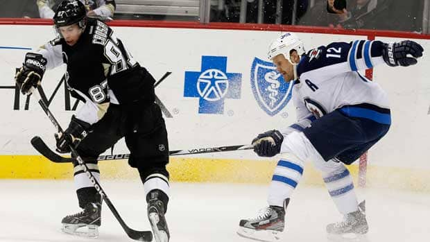 Pittsburgh Penguins forward Sidney Crosby, left, twists to reach the puck in front of Winnipeg Jets Olli Jokinen in the first period in Pittsburgh, Penn. on Thursday. (Jason Cohn/Reuters).