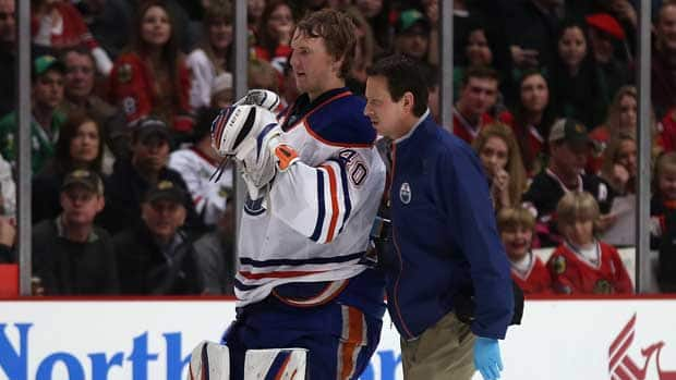 Edmonton Oilers goalie Devan Dubnyk is escorted off the ice after being injured against the Chicago Blackhawks at the United Center on Sunday in Chicago, Ill. (Jonathan Daniel/Getty Images)