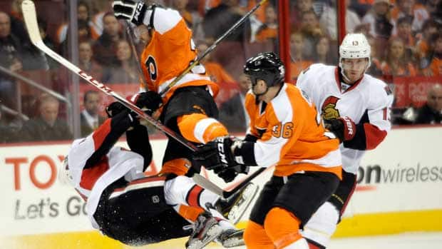 Philadelphia Flyers' Harry Zolnierczyk, centre, collides with Ottawa Sentors' Mike Lundin, left, in front of Flyers' Zac Rinaldo (36) and Senators' Peter Regin (13), during the first period on Saturday in Philadelphia. (Michael Perez/Associated Press)