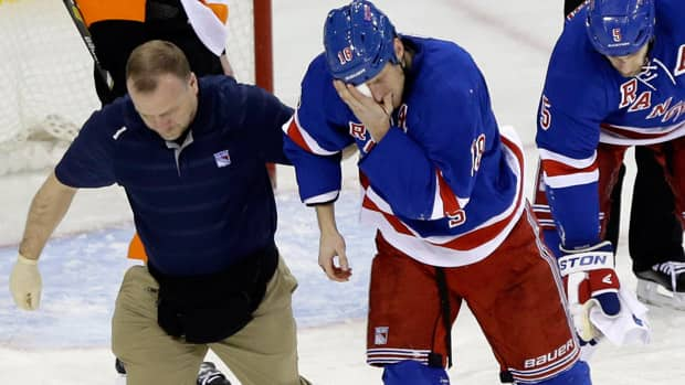 New York Rangers defenceman Marc Staal is helped by a trainer after taking a puck to the face in the third period against the Philadelphia Flyers on Tuesday in New York. (Frank Franklin II/Associated Press)