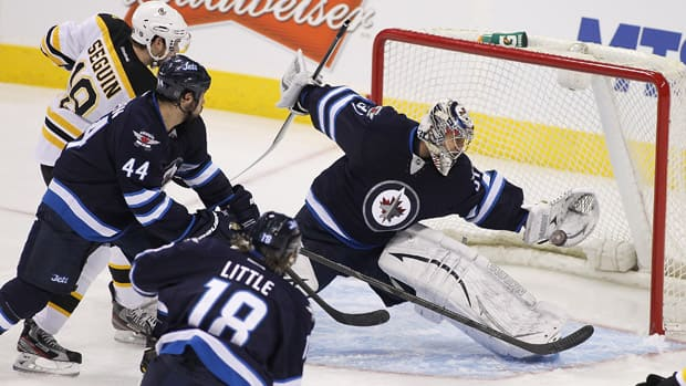 Jets goaltender Ondrej Pavelec, right, makes a brilliant glove save against the Boston Bruins Tuesday night in Winnipeg. (Marianne Helm/Getty Images)