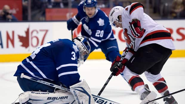 Toronto Maple Leafs goaltender James Reimer, left, makes a save on New Jersey Devils centre Stephen Gionta in Toronto on Monday March 4, 2013. (Frank Gunn/The Canadian Press)