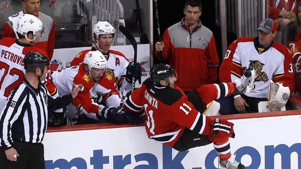 Panthers defenceman T. J Brennan 'helps' the Devils' Stephen Gionta get out of the Florida bench on Saturday. (Jason DeCrow/Associated Press)