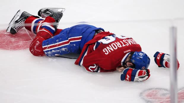 Montreal Canadiens forward Colby Armstrong lies on the ice after a hard collision with Carolina Hurricanes right wing Patrick Dwyer Monday night at the Bell Centre. (Christinne Muschi/Reuters)