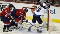 Captials defenceman John Eskrine (4) sweeps the puck away from the goal-line, while Winnipeg's Blake Wheeler raises his hands for a premature celebration Tuesday night in Washington. (Kevin Lamarque/Reuters)