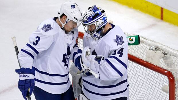 Toronto Maple Leafs goalie James Reimer, right, is congratulated by teammate Dion Phaneuf after the Maple Leafs defeated the Boston Bruins 2-1 in Game 5 in Boston on Friday. (Charles Krupa/Associated Press)