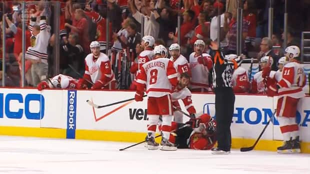 Referee Stephen Walkom blows the play dead to to call coincidental minor penalties in front of the Detroit Red Wings bench and negate the Chicago Blackhawks' tie-breaking goal late in the third period. (CBC Sports)