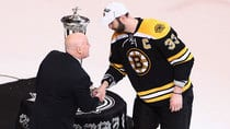 NHL Deputy Commissioner Bill Daly shakes hands with Zdeno Chara of the Boston Bruins in front of the Prince of Wales Trophy after the Bruins swept the Pittsburgh Penguins at TD Garden on Friday in Boston. (Alex Trautwig/Getty Images)