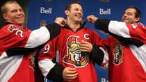 Newly appointed captain Jason Spezza, middle, gets his collar adjusted by assistants Chris Neil and Chris Phillips on Sept. 14. (Fred Chartrand/Associated Press)