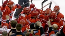 Manny Malhotra (22) is mobbed by Hurricanes teammates after scoring the OT winner in a 2-1 win over the Flyers on Tuesday. (Gerry Broome/Associated Press)
