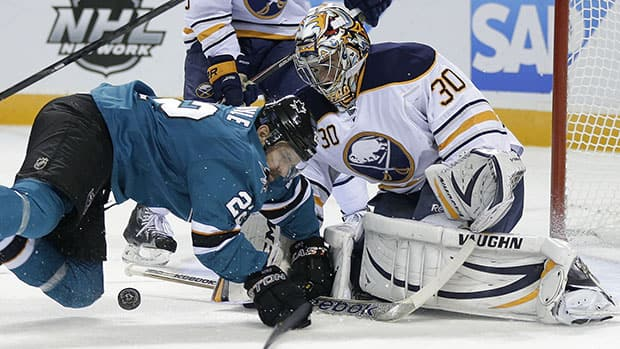 Buffalo goalie Ryan Miller makes a save on San Jose's Dan Boyle during the first period of Tuesday night's game. Controversy game later when the Sharks appeared to score in overtime. (Marcio Jose Sanchez/Associated Press)