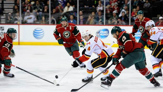 Kris Russell (4) of the Flames stickhandles through a crowd in a 5-1 loss to the Wild at Xcel Energy Center on Tuesday night. (Hannah Foslien/Getty Images)