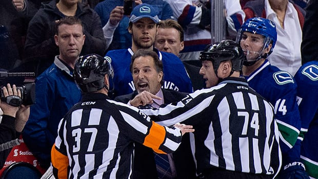 Referees get in the way of Vancouver Canucks head coach John Tortorella as he screams at the Calgary Flames bench at Rogers Arena in Vancouver, B.C. Saturday, January 18, 2014. (The Canadian Press)