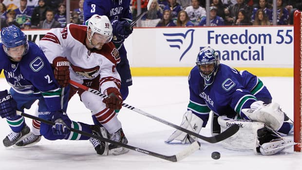 Roberto Luongo, right, makes a kick save on Coyotes forward Mikkel Boedker in a 5-4 Canucks victory in overtime on Sunday. (Ben Nelms/Getty Images)