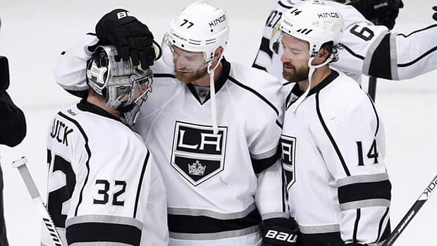 Kings forwards Jeff Carter (77) and Justin Williams (14) celebrate the team's 6-2 victory over the Chicago Blackhawks with goalie Jonathan Quick Wednesday night. (Charles Rex Arbogast/Associated Press)