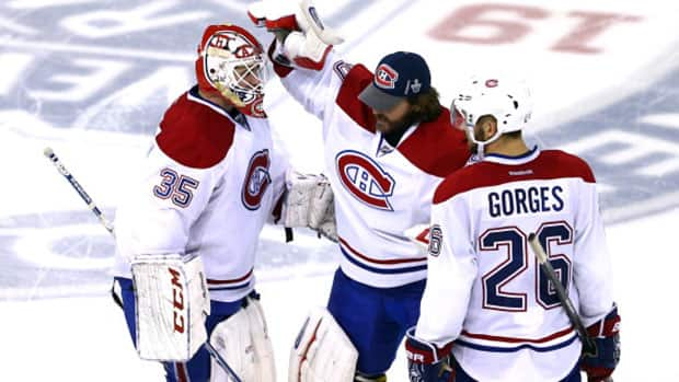Canadiens goaltender Dustin Tokarski (35) is congratulated by backup netminder Peter Budaj (30) and defenceman Josh Gorges after an outstanding Game 3 performance against the New York Rangers Thursday night. (Elsa/Getty Images)