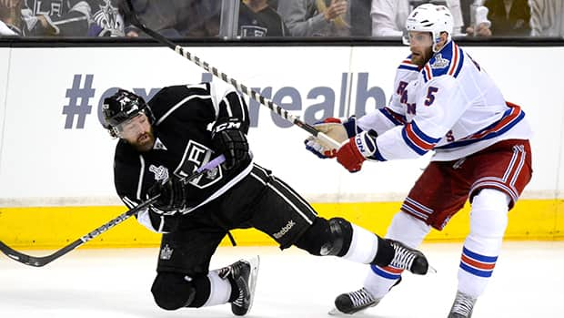 Justin Williams (14) of the Los Angeles Kings is checked by Dan Girardi (5) of the New York Rangers in the third period during Game 1 on Wednesday in Los Angeles. A miscue by Girardi led to Williams scoring against the Rangers in overtime. (Kevork Djansezian/Getty Images)