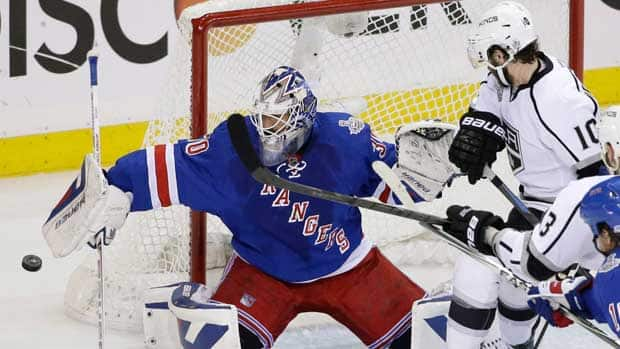 New York Rangers goalie Henrik Lundqvist blocks a shot as Los Angeles Kings centre Mike Richards looks for the rebound in the first period during Game 4. (Frank Franklin II/The Associated Press)
