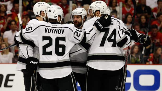 Justin Williams, middle, of the Los Angeles Kings celebrates with his teammates after scoring in a 5-4 overtime win over the Chicago Blackhawks in Game 7 of the Western Conference final at United Center on Sunday. (Nam Y. Huh/Associated Press)