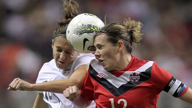 Canada's Christine Sinclair, right, and Carli Lloyd of the U.S. fight for the ball during the CONCACAF Women's Olympic Qualifying Tournament at BC Place in Vancouver on Sunday. Both teams earned Olympic berths to London 2012 and Canada learned a few important lessons along the way. (Jonathan Hayward/Canadian Press)