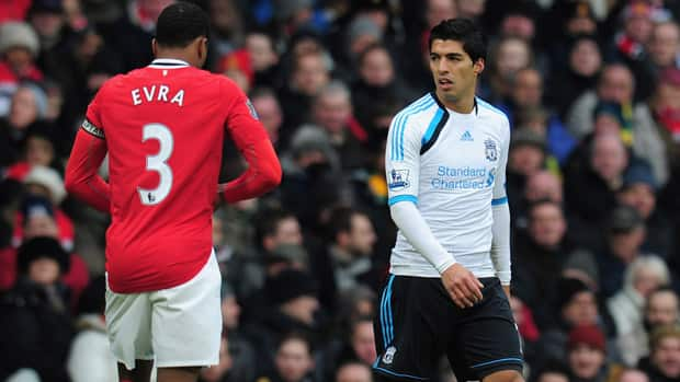 Liverpool's Luis Suarez, right, was banned for eight games after being found guilty of racial abuse against Manchester United defender Patrice Evra (3) during a Premier League match last October. (Shaun Botterill/Getty Images)
