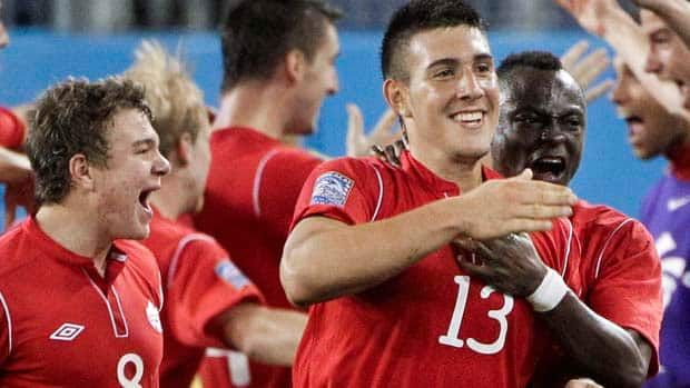 Canada's Lucas Cavallini (13) celebrates with Samuel Piette (8) and Randy Edwini-Bonsu (19) after Cavallini scored a goal against the United States in the second half of a CONCACAF Olympic qualifying soccer match on Saturday in Nashville, Tenn. Canada won 2-0. (Mark Humphrey/Associated Press)