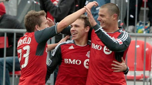 Danny Koevermans, right, celebrates one of his team-leading eight goals last season with teammates Terry Dunfield, left, and Matt Stinson. Koevermans played in just 10 of the Toronto FC's 34 MLS games last season, leaving many soccer enthusiasts wondering what the Dutchman can do with a full slate of games. (Abelimages/Getty Images)
