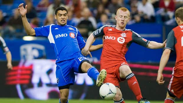Montreal Impact's Lamar Neagle, left, and Toronto FC's Richard Eckersley battle for the ball during action in Montreal, Saturday, April 7, 2012. (The Canadian Press/Graham Hughes)
