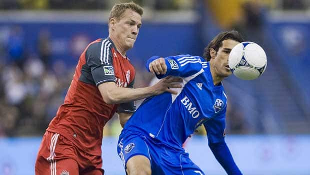 Montreal Impact's Bernardo Corradi, right, and Toronto FC's Ty Harden battle for the ball during first half MLS soccer action in Montreal on Saturday. (Graham Hughes/Canadian Press)