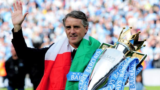 Manchester City manager Roberto Mancini celebrates with the trophy after winning the Premier League title on Sunday.  (Shaun Botterill/Getty Images)
