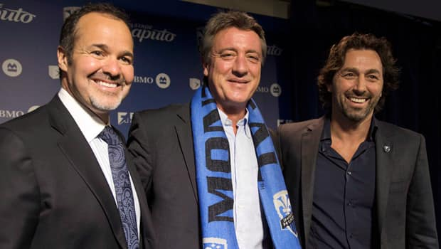 Newly hired head coach Marco Schallibaum, wearing scarf, is flanked by Impact chairman Joey Saputo, left, and sporting director Nick Di Santis during an introductory media conference in Montreal on Tuesday. (Ryan Remiorz/Canadian Press)