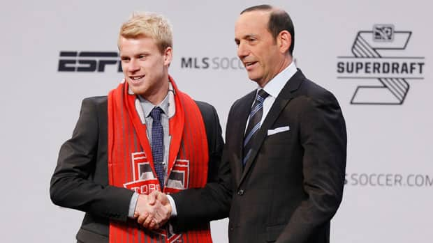 Canadian midfielder Kyle Bekker, left, shakes hands with MLS commissioner Don Garber after being selected by Toronto FC with the third overall draft pick. (Joe Robbins/Getty Images)