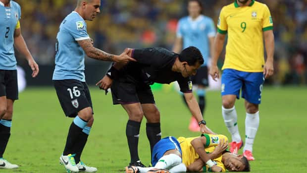 Referee Enrique Osses, middle, reacts following a tackle on Brazilian striker Neymar, bottom right, during Wednesday's Confederations Cup semifinal against Uruguay. (Scott Heavey/Getty Images)