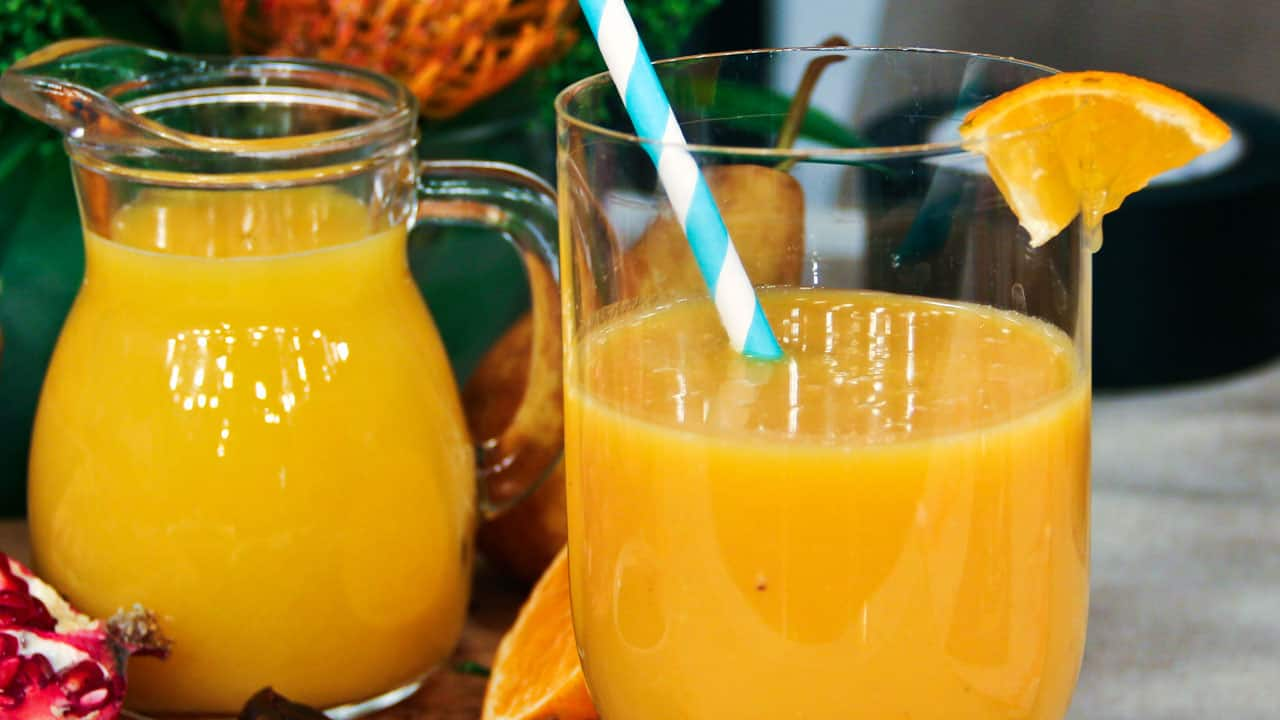 Orange smoothie in a glass with a blue and white straw,