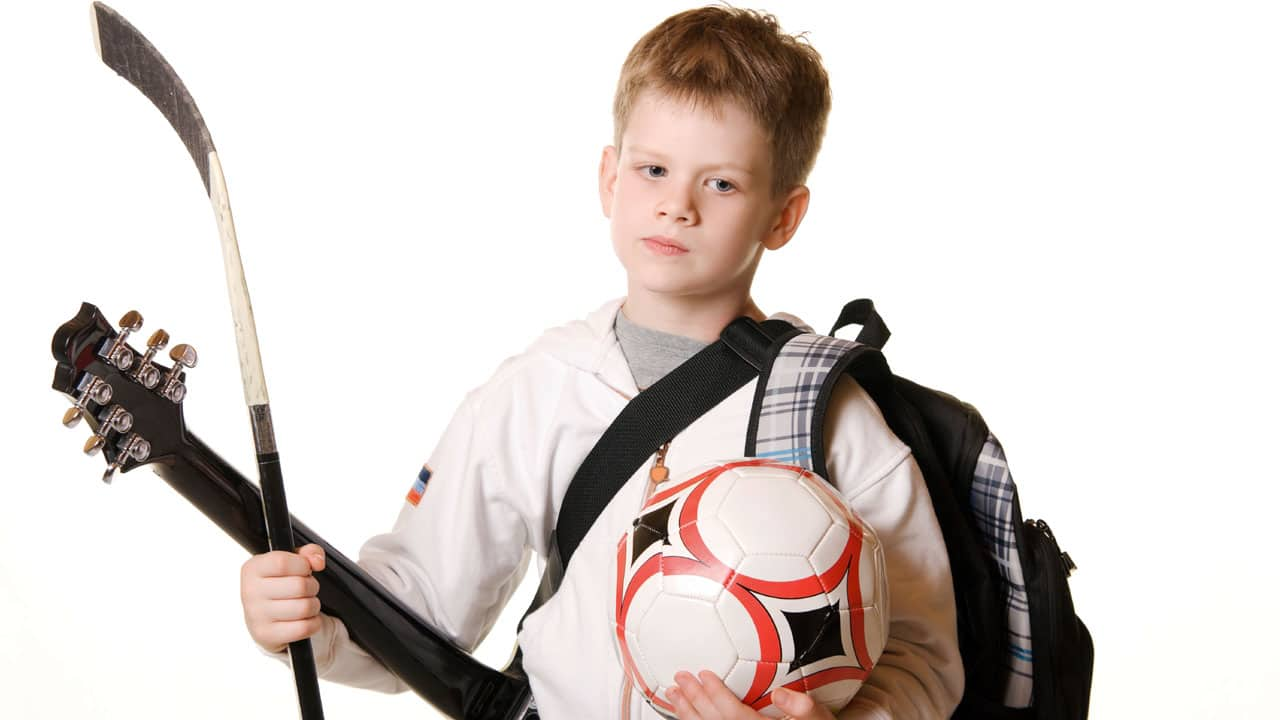 A young boy holds a hockey stick, guitar, soccer ball and a backpack. He looks tired.
