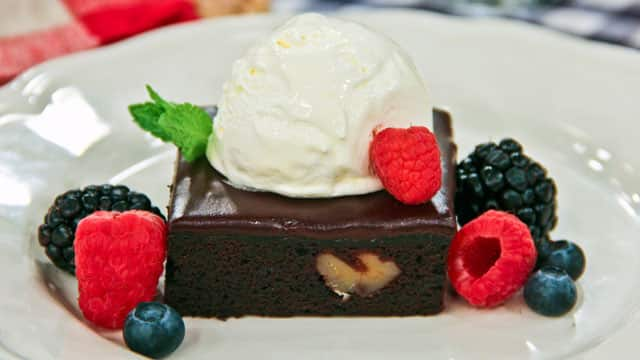 A square piece of brownie topped with chocolate icing and a scoop of vanilla ice cream. The brownie is garnished with a few raspberries, blackberries, and blueberries.