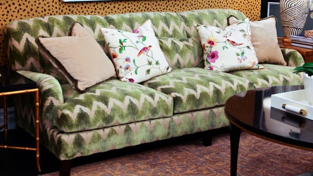 High-end couch with a moss green and beige zig-zag pattern.