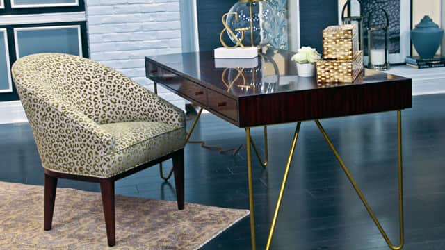 Leopard print chair with a mahogany wood desk.