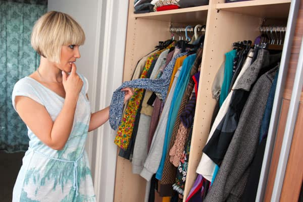 Woman puzzles over her closet's contents.