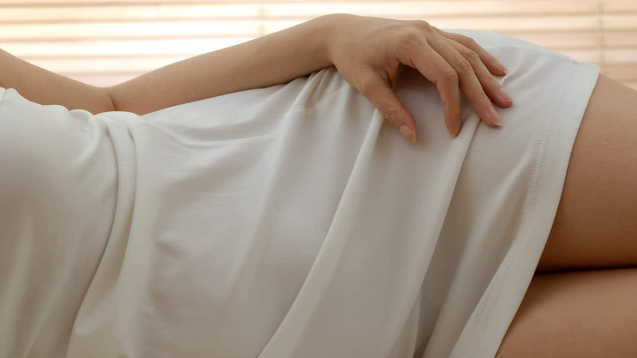 Woman in white dress lies sideways on a bed with her hand placed on her thigh.